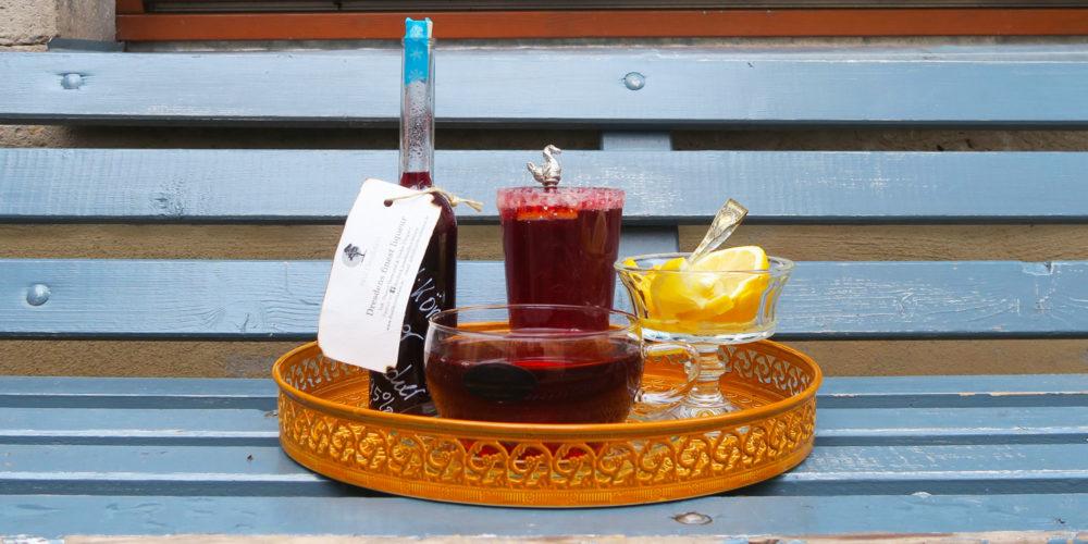 Teelikör, Tee und Cocktail auf Tablett.