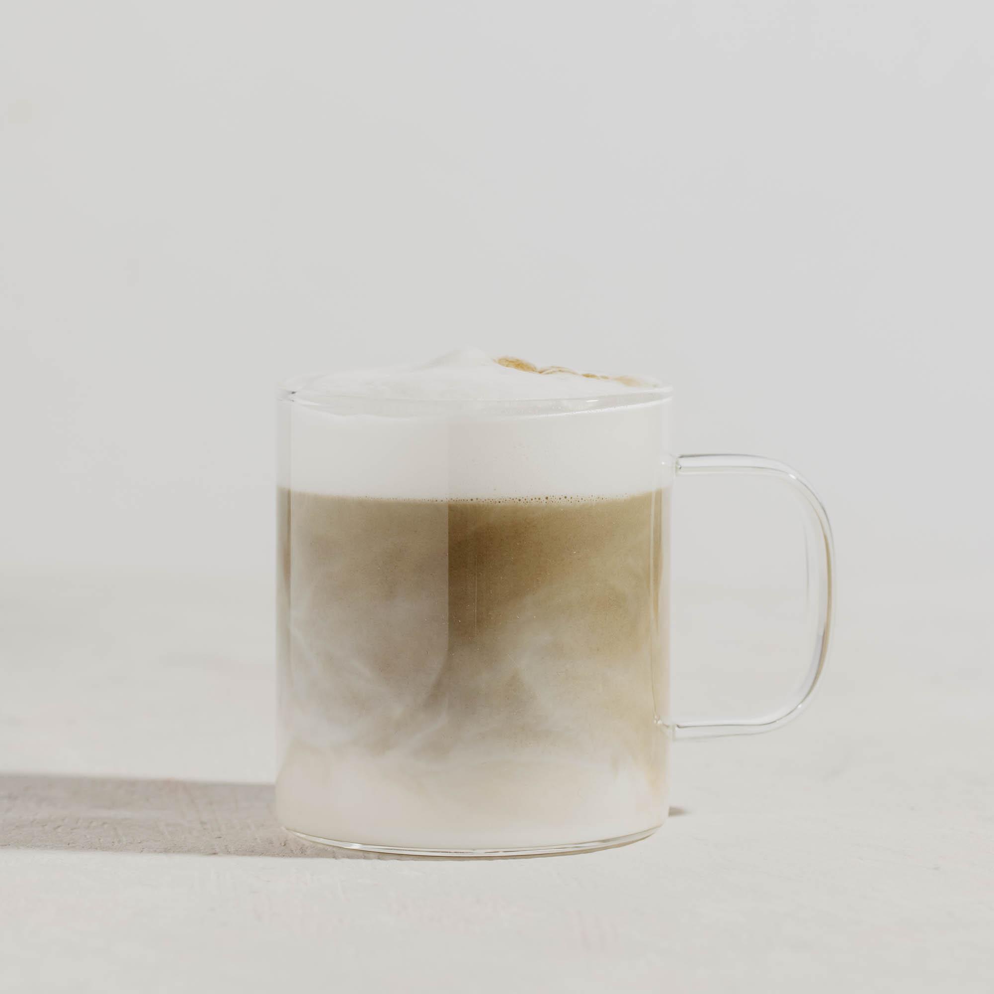 Glastasse mit Houjicha Latte und Schaumkrone auf weiß