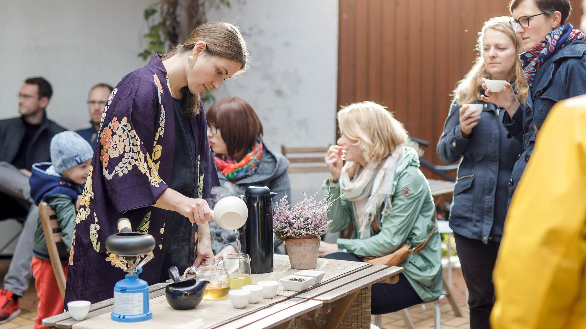 Frau beim aufgiessen von Tee