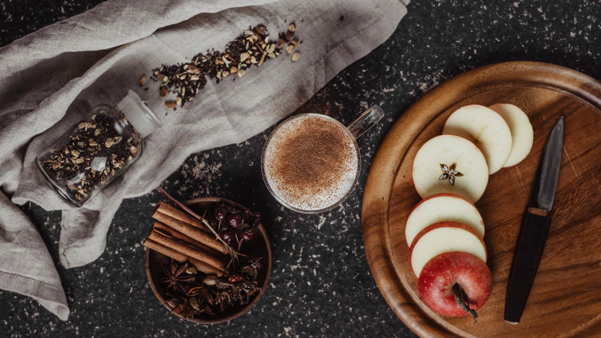Chai Latte in Glas neben Holzbrett mit aufgeschnittenem Apfel und Chai Gewürzmischung