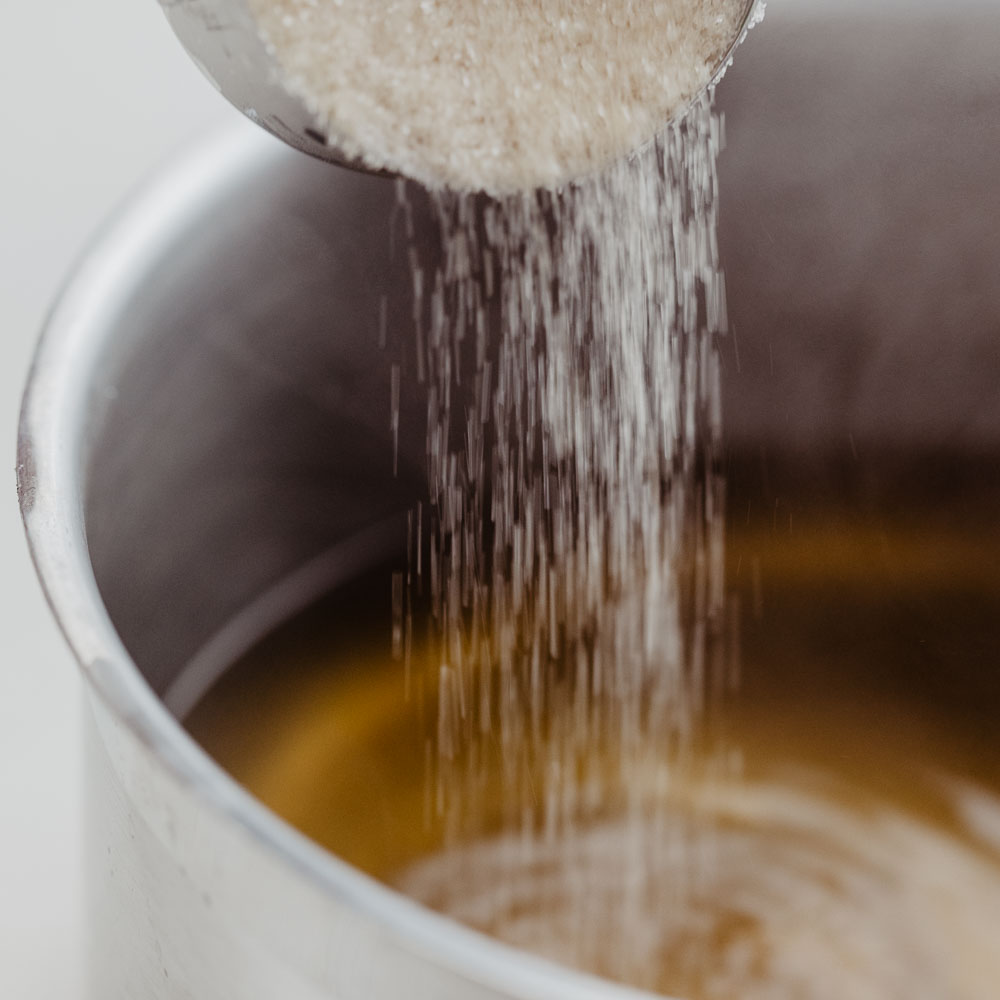 Zucker wird in Topf mit gelber Flüssigkeit gegeben
