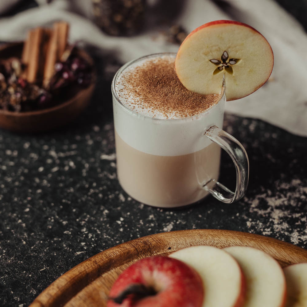 Chai Latte in Glas Tasse mit Apfelschnitz am Rand