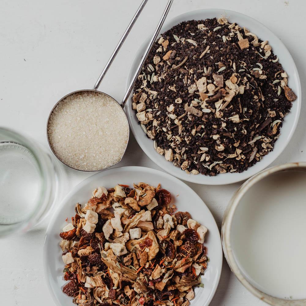 Loser Früchtetee und Schwarzer Tee auf weißen Porzellantellern