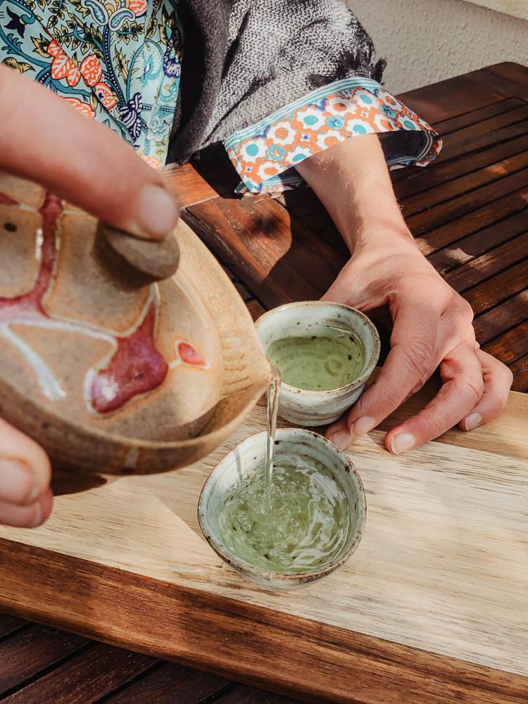 Grüner Tee in Schale gegossen
