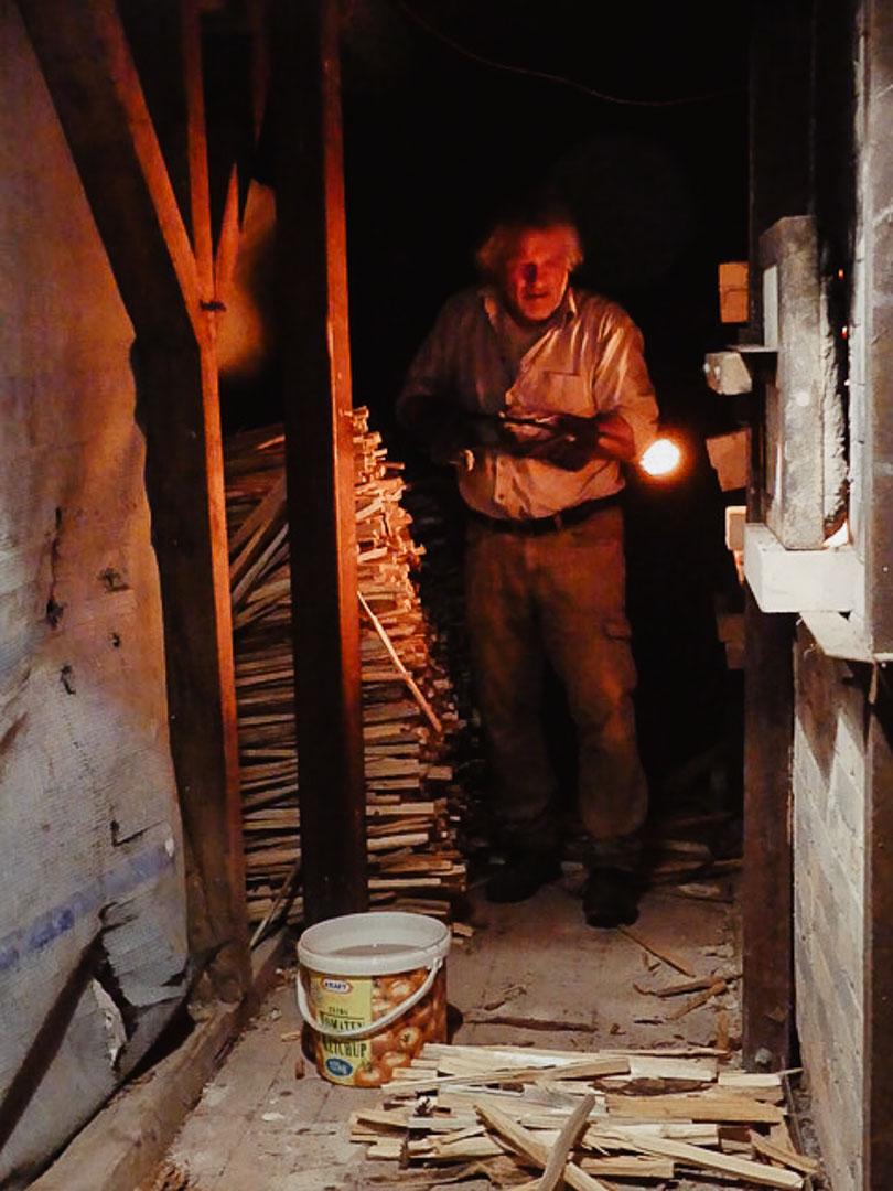 Hendrik Schöne nimmt ein weiß glühendes Keramikstück aus dem Ofen