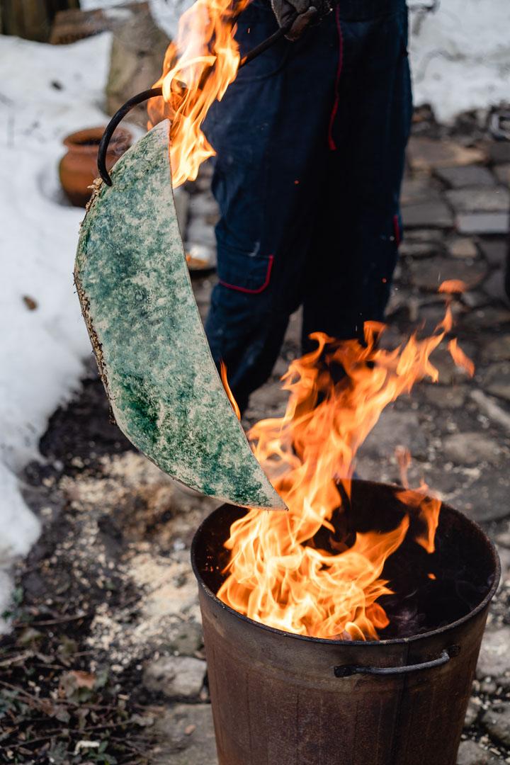 Grüne Vase im Feuer über Metalleimer