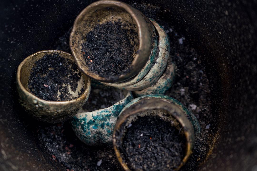 gestapelte Raku-Keramik in Eimer mit Asche überzogen