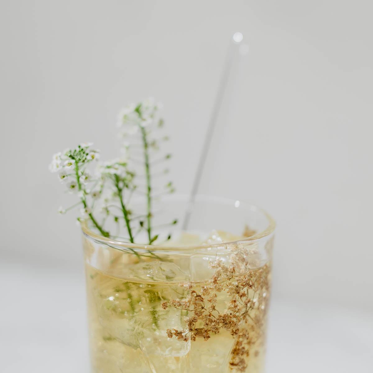 Gelber Cold brew mit Eiswürfel im Glas