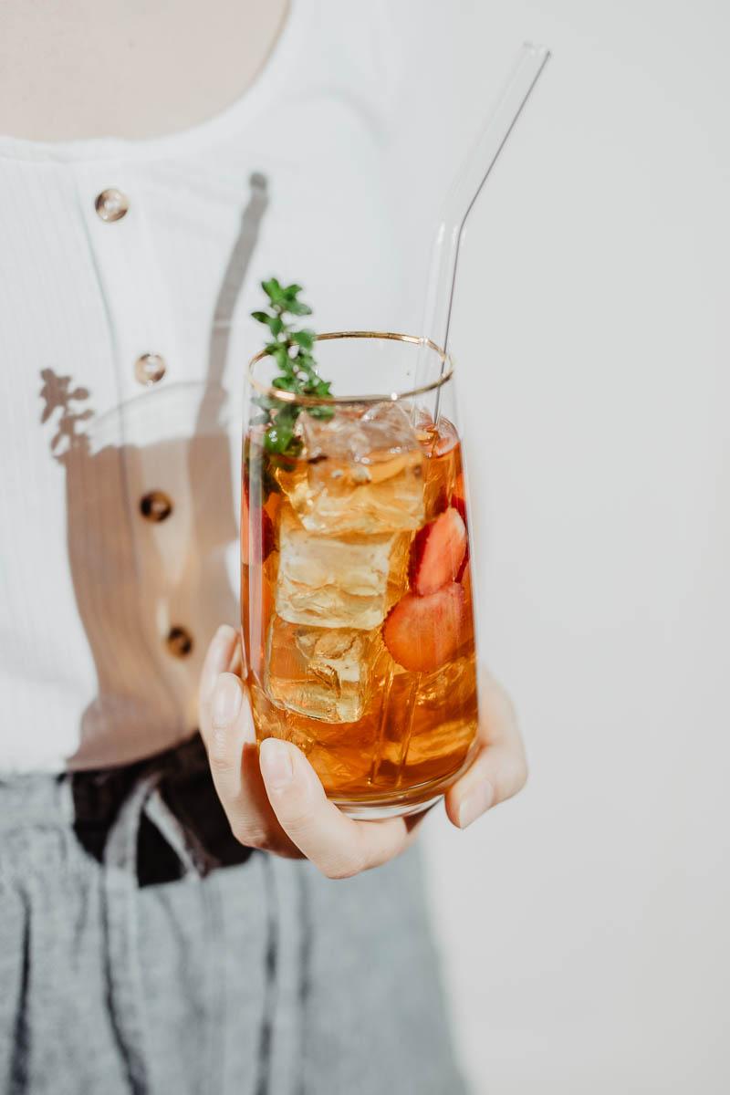 Glas mit Eistee von Hand gehalten