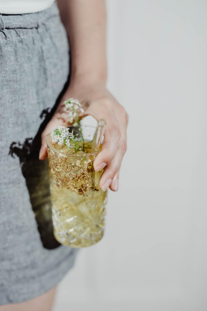Glas mit Blüten und Cold Brew von Hand gehalten