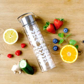 Eisteeflasche mit Obst und Kräutern