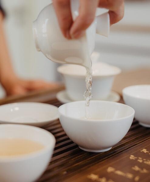 Tee wird aus Gaiwan in Porzellanschale gegossen
